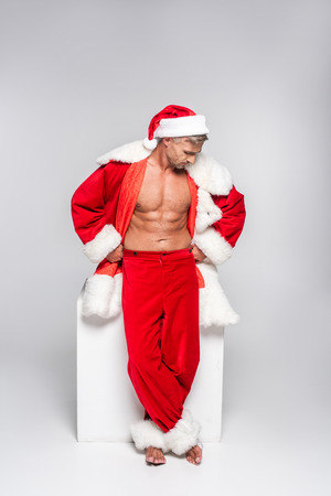 Sexy barefoot man in Santa costume posing in studio and looking away on grey background