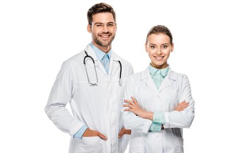 Knappe gelukkige mannelijke arts permanent in de buurt van vrouwelijke collega met gekruiste armen geïsoleerd op witte achtergrond
