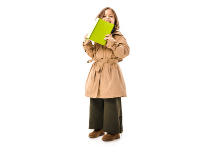 Happy little child in trench coat with book looking at camera isolated on white background 版權商用圖片
