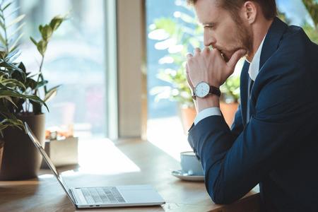 Vista laterale dell'uomo d'affari premuroso che guarda lo schermo del laptop al tavolo con una tazza di caffè al bar Archivio Fotografico