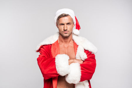 Serious handsome man in Santa costume standing with crossed arms and looking at camera isolated on grey background
