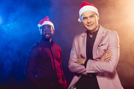 6f025c88a5254 Handsome man in pink jacket and Santa hat standing near African American  friend on black with
