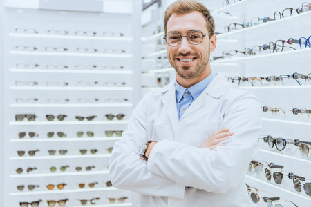 Portrait of smiling professional optometrist in glasses posing with crossed arms in ophthalmic shop Stock Photo