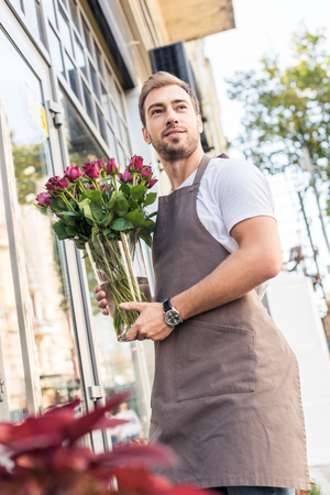 Low angle view of florist holding glass jar with burgundy roses near flower shop Stok Fotoğraf - 110354997