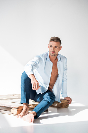 Handsome sexy man sitting on wooden pallet on white background and looking away