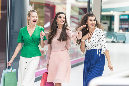 Excited young women holding paper bags and looking away while walking together in shopping mall