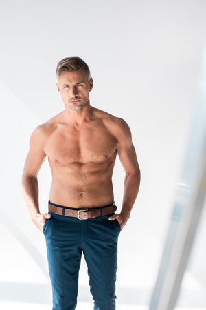 Serious shirtless adult man looking at camera on white background