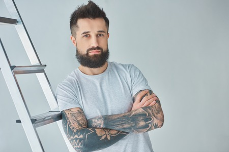 Handsome bearded tattooed young man standing with crossed arms near stepladder and looking at camera on grey background Reklamní fotografie