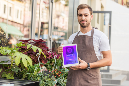 Handsome florist holding tablet with shopping appliance near flower shop Stok Fotoğraf