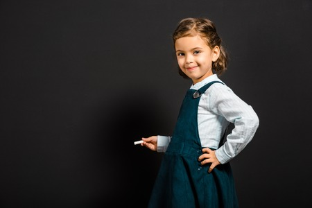 Smiling schoolgirl with piece of chalk standing at blank blackboard