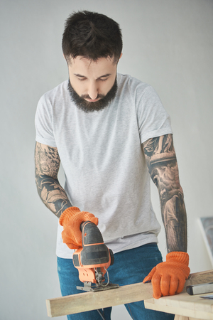 Handsome bearded tattooed man holding wooden plank and using electric jigsaw