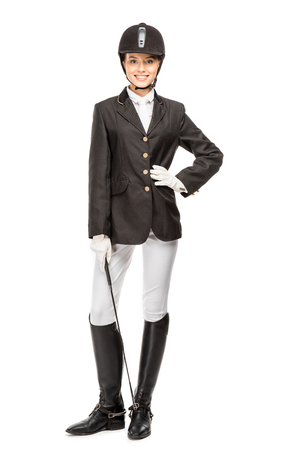 Smiling young horsewoman in uniform holding horseman stick and looking at camera isolated on white background Banco de Imagens