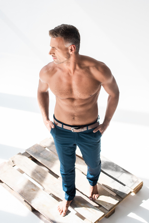 High angle view of shirtless handsome adult man standing on pallet on white background and looking away Stock Photo