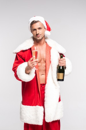 Handsome sexy Santa holding glass and bottle of champagne and looking at camera isolated on grey background Stock Photo