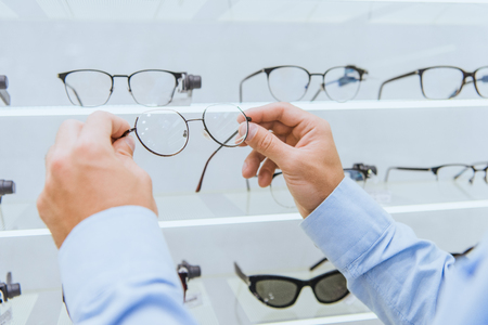 Cropped image of man taking eyeglasses from shelves in ophthalmic shop