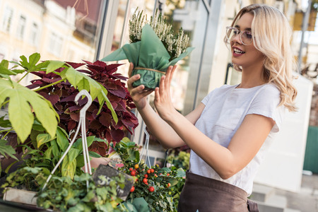 Side view of attractive florist looking at potted plant near flower shop Stok Fotoğraf - 110355182