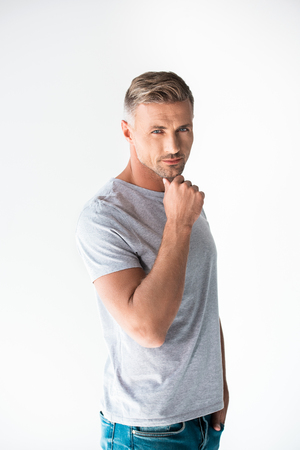 Thoughtful adult man in blank grey t-shirt looking at camera with hand on chin isolated on white background