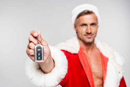 Close-up view of handsome man in Santa costume holding car key and looking at camera isolated on grey background