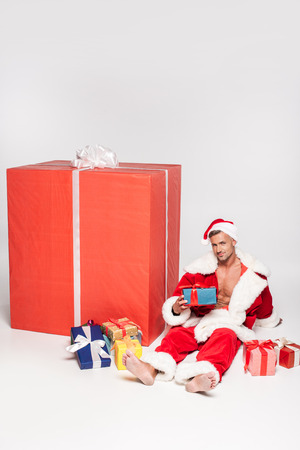 Handsome man in Santa costume sitting with various Christmas presents and smiling at camera on grey background