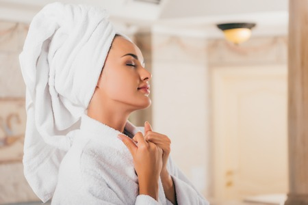 Beautiful woman relaxing with towel on head at spa salon