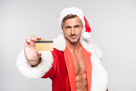 Handsome man in Santa costume holding credit card and smiling at camera isolated on grey background