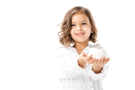Cute kid in white bathrobe showing body cream in hands isolated on white background