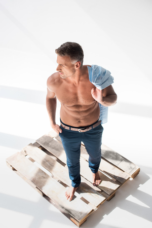 High angle view of shirtless sexy adult man standing on pallet on white background Stock Photo - 110355335