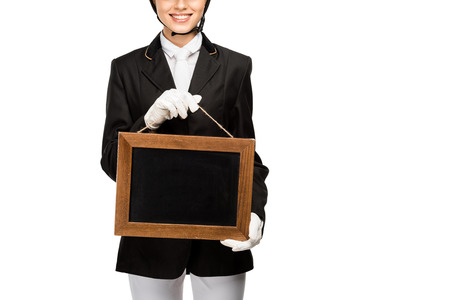 Cropped shot of smiling young horsewoman in uniform holding blank chalkboard isolated on white background Banco de Imagens