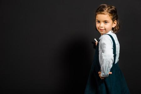 Schoolgirl with piece of chalk standing at blank blackboard Фото со стока