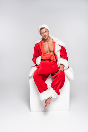 Sexy man in Santa costume sitting with red bag and looking at camera on grey background Archivio Fotografico