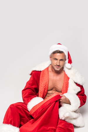 Handsome man in Santa costume sitting with red bag and smiling at camera isolated on grey background