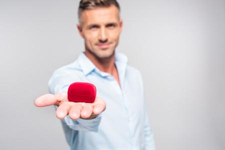 Inquadratura ravvicinata di un bell'uomo adulto che tiene in mano una scatola rossa per la proposta isolata su sfondo bianco