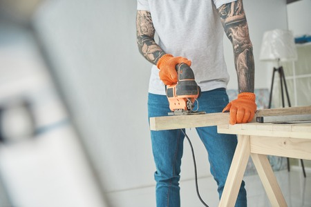 Cropped shot of young tattooed man using electric jigsaw during home improvement