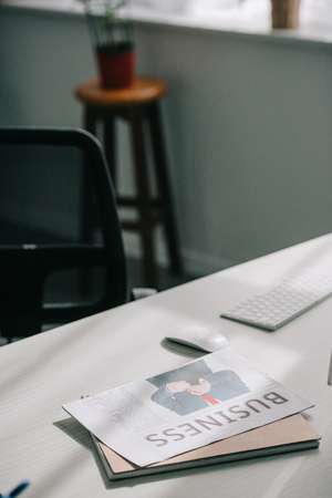 Business newspaper and computer on tabletop in business office Stock Photo
