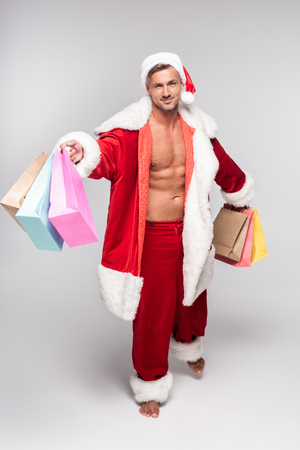 High angle view of handsome barefoot man in Santa costume holding shopping bags and smiling at camera on grey background