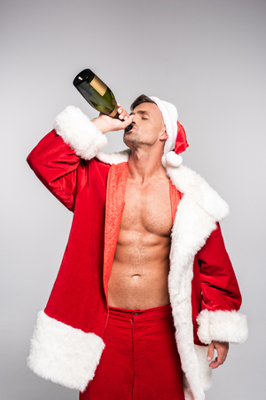 Handsome sexy man in Santa costume drinking champagne from bottle isolated on grey background Stock Photo