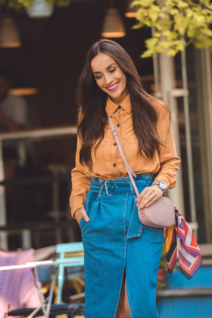 Happy fashionable young woman with stylish handbag at urban street Stockfoto