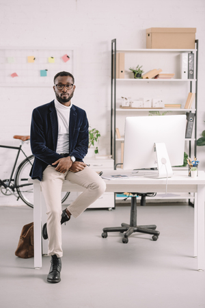 Stylish African American businessman leaning on table with computer in modern office Stock Photo