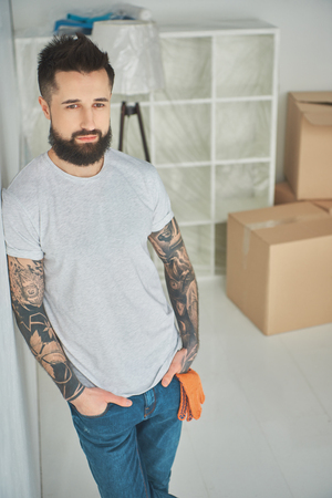 Handsome bearded tattooed man standing with hands in pockets in new house