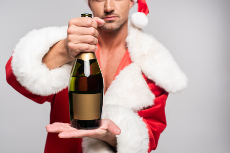 Cropped shot of man in Santa costume holding bottle of champagne with blank label isolated on grey background