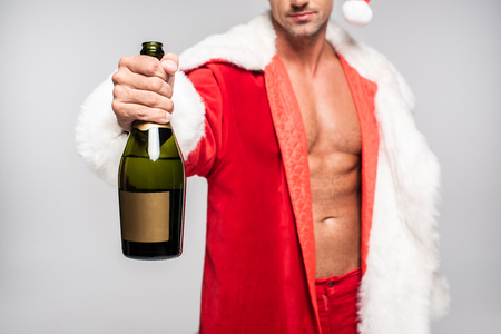 Cropped shot of sexy Santa holding bottle of champagne with blank label isolated on grey background