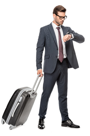 Handsome young businessman with luggage looking at wrist watch isolated on white background