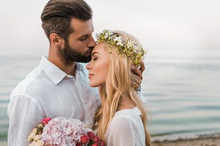 Zijaanzicht van de knappe bruidegom die het voorhoofd van de aantrekkelijke bruid kust op het strand
