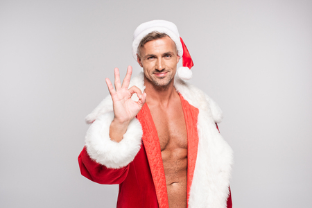 Handsome happy Santa showing ok sign and smiling at camera isolated on grey background Stock Photo