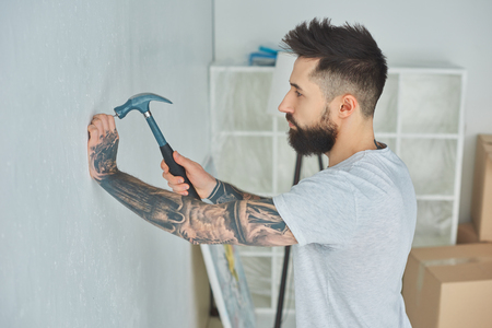 Side view of bearded young man hammering nail at wall 写真素材