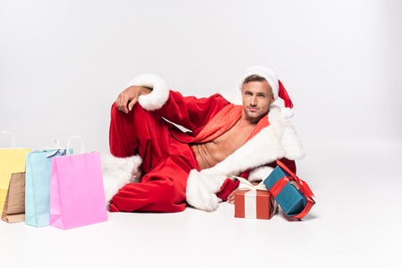 Handsome man in Santa costume lying with gift boxes and shopping bags on grey background