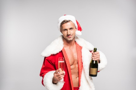 Handsome man in Santa costume holding glass and bottle of champagne isolated on grey background Stock fotó