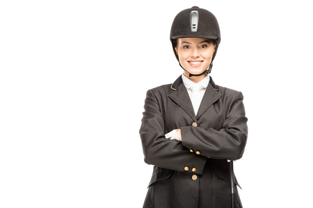 Happy young horsewoman in uniform and helmet looking at camera with crossed arms isolated on white background Banco de Imagens
