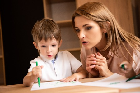 Surprised educator looking at boy drawing in kindergarten