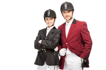 Successful young equestrians in uniform and helmets looking at camera isolated on white background